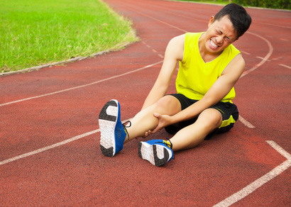 young male runner suffering from leg cramp on the track